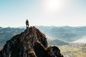 Mand på toppen af bjerg.